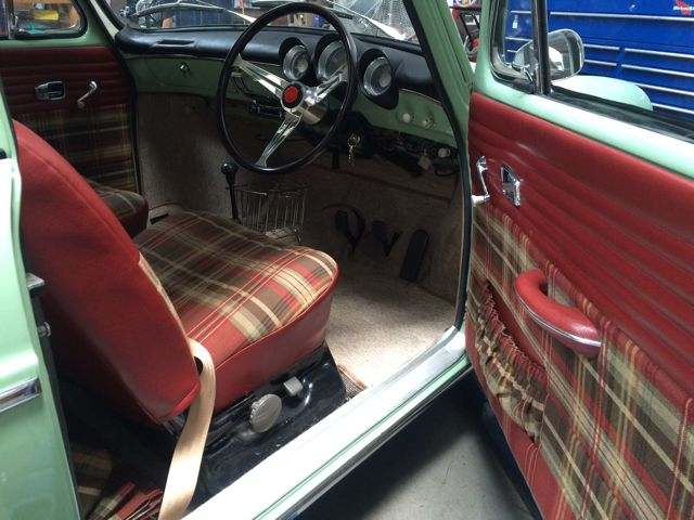 Interior is very unique with red and tan plaid, tan rugs, white headliner and black controls.